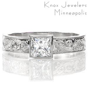 This solitaire design features a wide, flat band crowned with a 0.75 carat princess cut center diamond. The band is embellished with stunning, intricate hand engraved designs and the edges are refined with milgrain texture. The pattern on the band adds an artistic appeal to the overall piece.