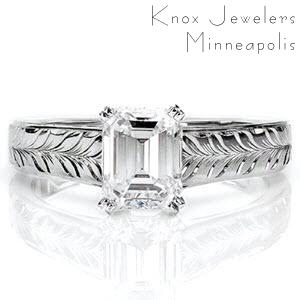 This traditional ring includes a lovely long faceted emerald cut 1.0 carat center diamond held in a four prong setting. The linear quality of the center stone is mimicked in the straight shank with comfort fit interior. The top face contains bright cut hand engraving in a modified wheat pattern.