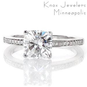 The 1.50 carat cushion cut diamond is finely contoured in this lovely contemporary design. Multi-faceted diamonds are bead set along the length of the band to embellish the brilliance of the center stone. The row of micro pavé stones between each prong is a graceful touch to this elegant design.