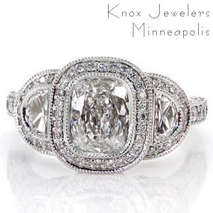 This tantalizing design puts all the focus on the 1.00 carat cushion cut center diamond. On either side of center is a half-moon diamond in a micro pavé halo. The band is lavishly adorned with diamonds on the top and sides. The halo displays pockets of filigree and a butterfly shape for a picturesque side view.