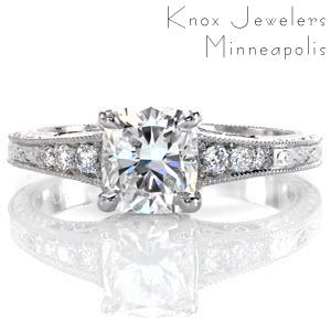 The beautiful shape of the 1.00 carat cushion cut center diamond is splendidly accented by the tapered band of the ring. The bead set side stones taper down in size as well and hand engraving finishes the detailing on top and sides of the band. Filigree curls on the sides add a final delicate touch.
