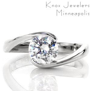 This unique engagement ring features a wrapped half bezel setting that has the look of a tension setting, but is more secure. The high polish finish of the flowing band creates a sleek transition for the eye to focus upon the flashes of color projecting from the center stone.