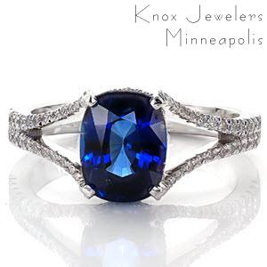 Our Royal Blue design emits regal elegance with rich velvety blue tones. The center stone is a beautiful 2.0 carat cushion cut sapphire set in a four prong setting with micro pavé diamond under bezel. The diamonds continue along the split-shank band design that is gracefully frames the sapphire.