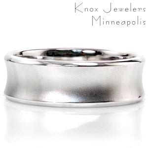 This concave design uses texture to create detail. The outer edges are sleek with a high polish while the middle of the ring is sand blasted with a matte finish. The inside of the ring is slightly rounded for comfort. This 14k white gold design can be customized in width and metal type.