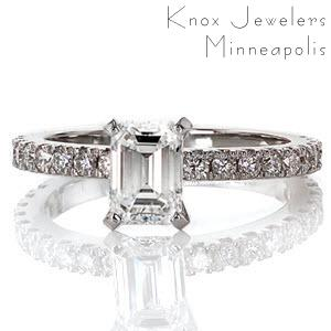 This beautiful diamond engagement ring features a micro pave band set with an emerald cut center stone. The mirrored facets of the step-cut center diamond are vibrantly contrasted by the scintillation and fire of the small round diamonds on the band.