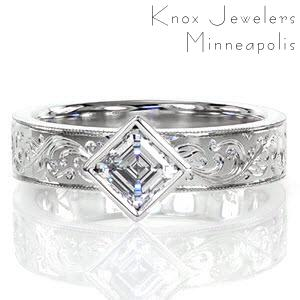 Enthralling elements combine to form this breathtaking ring. A 0.75 carat asscher cut solitaire, bezel set, in a kite position is the focal point with its cascading, step-like facets. The wide band is embellished with mesmerizing, intricate hand engraved patterns that flow out from the center.