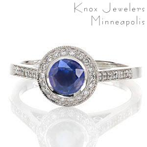 The Filigree Enchantment design has a classic full bezel surrounding the 0.60 carat round natural blue sapphire. Adding to the divine design is a full circle halo of micro pavé diamonds, hand wrought filigree scrolls and two full bezel set surprise diamonds.