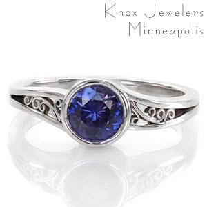 The purplish blue 1.00 carat sapphire is encircled in a full bezel to emphasize the mysterious color of the center gemstone. The open split shank is decorated with hand-formed filigree for a picturesque view. The high polish of the edges is a sleek finish to this sophisticated design.
