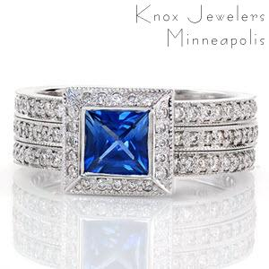 Magnificent lines of milgrain outline round bright-cut and bead-set micro pavé diamond bands that are joined into one distinctive wide band. Set atop the perfect square halo is a natural 0.75 princess cut blue sapphire. Crafted in 14k white gold, the full bezel captures the sapphire and completes a uniform design.