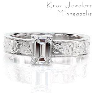 Lorrie features a sophisticated 0.75 carat emerald cut diamond. The long rectangular facets descend towards the center of the stone to accentuate its luster and whiteness. The extravagant pattern of the hand-carved engraving and the textured milgrain edges possess a vintage charm.