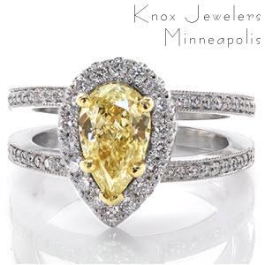 Stunning pear cut yellow diamond with yellow gold prongs on a white gold halo and micro pave band.