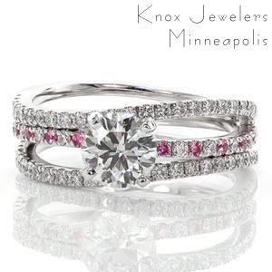Starfish has a serene wave of three micro pavé diamond bands. As the center band is accented with round cut pink sapphires, a stunning 1.00 carat round brilliant cut diamond is set to accent the graceful flow of the ring. The three bands are joined as one at the bottom and crafted in 14k white gold.