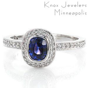 The soft curves of a regal 0.75 cushion cut blue sapphire shape the layout of Design 2048. In 14k white gold, the full bezel halo is surrounded by micro pavé diamonds. Formal lines of the micro pavé band create a pedestal for the halo, providing a striking profile and area for additional bands.