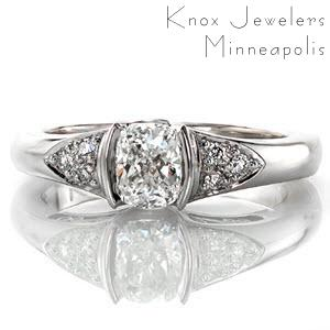 This charming design melds simple details to create a beautiful design. The 0.75 carat cushion cut center stone is held in a half-bezel setting and flanked on either side by a cluster of three round diamonds. The profile reveals graceful hand-formed filigree which adds a vintage feel to the ring.