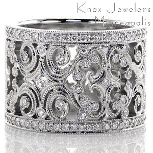 Caledonia is a sensational ring fashioned from large, intricate filigree curls and diamonds. The edges of the pattern are textured with milgrain to refine the look, and there are small bezel set diamonds throughout the band. Each edge of the band is finished with a row of micro pavé to frame the design.