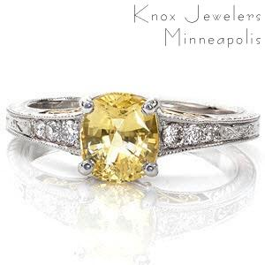 This mesmerizing design is a two-tone 14k yellow and white gold combination. The center stone is a 1.00 carat cushion cut yellow sapphire in a tapered white gold band. Micro pavé diamonds accent the center stone. Hand engraving and yellow gold filigree curls add the perfect compliment.
