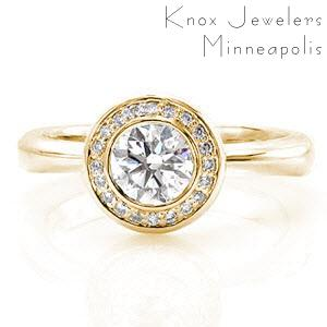 Yellow gold halo engagement ring with bezel set round diamond in Cleveland.