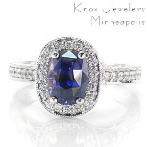 This sumptuous design uses little details to create an intricate piece. The luscious 1.50 carat cushion cut sapphire is a unique blue violet color that captures the eye. There are micro pavé diamonds set on the halo, band, and underneath the center setting. Hand wrought filigree and engraving complete the look.