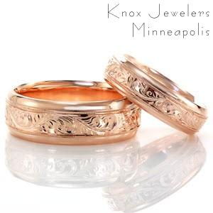 These beautiful wedding bands are made in 14k rose gold with intricate hand engraving adorning the middle of the rings. The delicate scroll pattern is edged on either side with milgrain texture to add a refined finish. The high polished outer edges add the perfect touch of shine to these classic wedding bands.