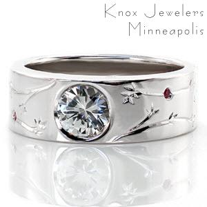 This wide contemporary band was custom designed with hand engraved organic patterns. There are lovely pink sapphires bezel set throughout the engraved design. The center stone is a bezel set 0.80 carat round brilliant cut diamond. The high polish of the ring creates a beautiful contrast with the details.