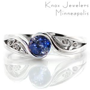 This mesmerizing solitaire design focuses on the luscious 0.80 carat round cut blue sapphire center. The band is a unique split shank with lots of movement and the ends flow around the center stone to form a half bezel setting. The pockets of the band are filled with graceful filigree curls.