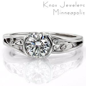 This is a stunningly elegant design. The 0.75 carat round brilliant cut center diamond is set in a half bezel that stays low to the finger. The split shank band has delightful handmade filigree in the pockets. Some of the curls are shaped like small leaves and have diamonds set in them.