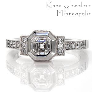 This design is inspired by the art deco style. The 0.75 carat asscher cut center stone is framed by a wide bezel which has been given a high polish to mimic the cascading, step cut facets of the diamond. The two bars to either side of center and the band are detailed with micro pavé and milgrain edging.