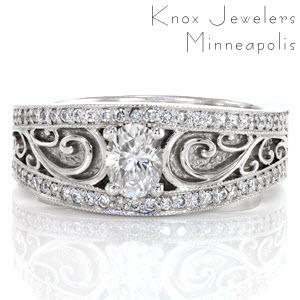 This dazzling ring uses lovely filigree curls to highlight the 0.50 carat oval cut center diamond. The center stone and filigree is encompassed by two rows of micro pavé with milgrain texture on the edges. These details blend seamlessly together to create a unique, antique inspired wide band.
