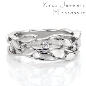 This nature inspired wide band is a graceful design that combines organic metal work detail within the unique pierced pattern. Diamonds are nestled among the woven vines and leaves for a touch of enchantment. The gentle flow of the pattern is mesmerizing.