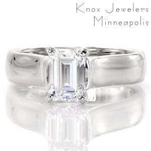 The Imperial design is a contemporary engagement ring with a wide, high polished band sweeping up to the cathedral setting of the emerald cut center stone. The luster of the metal perfectly compliments the mesmerizing mirror effect of the diamond's step-cut facets.