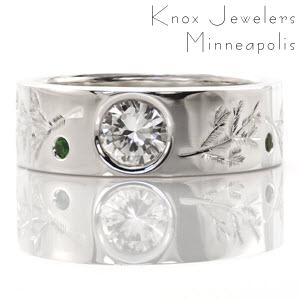 This custom design features unique engraved designs of pine branches. The center stone is a bezel set 0.80 carat round brilliant cut diamond. The wide band also has vivid green emeralds set in between the engraving. The wide band adds a contemporary touch to the ring.