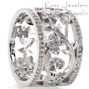 Unique custom wide band ring in Mission Viejo with bead set diamond rails surrounding a diamond set floral designed center.