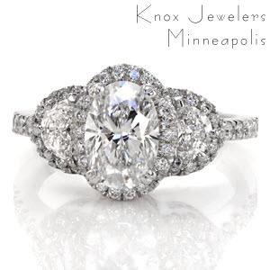 This halo engagement ring features a 1.00 carat oval shape center diamond and two half moon shaped diamonds. The center stone is set with a double prong on each corner. Around these three stones is a halo of micro pavé set diamonds. Both sides of the design feature hand wrought filigree in three pockets.