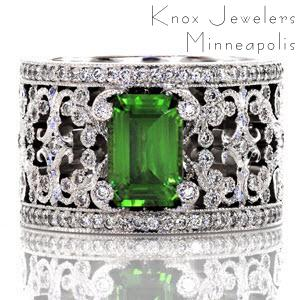 Intricate pierced scrolls created in 14k white gold and adorned with bead set diamonds. The Britty design showcases the emerald cut green gem stone with distinction by four diamond capped prongs. Two rails of shared prong round diamonds are finished with hand applied milgrain on our Knox Signature heirloom band.