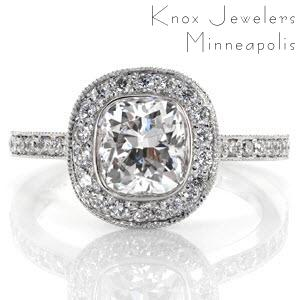 This design displays a sleek bezel around the cushion cut diamond. The silhouette of the stone is embellished with a halo of diamonds giving this ring a contemporary feel. Sitting high above the band, the halo allows for a matching wedding and anniversary band on each side of the ring.