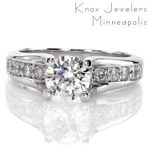 This magnificent design features a 1.00 carat round brilliant cut center diamond that is raised above the band. The prongs are formed from the high polished edges of the band which elegantly swoop up to display the center stone. The band is embellished with diamonds that go all the way under the center stone.
