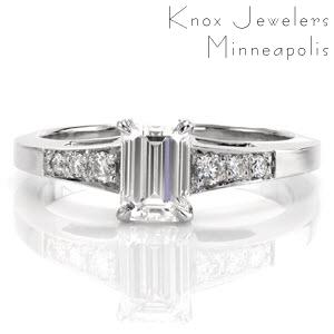 This elegant ring uses the smooth, straight lines of the band to compliment the straight lines of the 0.80 carat emerald cut center diamond. The three round brilliant cut diamonds on either side of the center stone are a beautiful contrast. These side stone graduate in size to match the slight flare of the band.