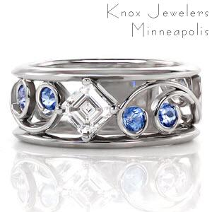 Classic filigree is paired with this modern wide band for stylish appeal. Each intricate curl is adorned with a Ceylon sapphire for a hint of color. Interwoven between the scroll patterns is a 0.50 carat asscher cut diamond. The linear parallel facets give this center stone the appearance that it goes on forever.