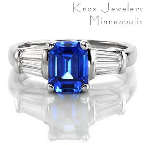 Design 2270 incorporates crisp faceting and elegant hues of an imperial blue hue seamlessly. A 2.00 carat emerald cut sapphire is set within a traditional four prong setting and framed with tapered baguettes. The 14k white gold band tapers for a comfortable fit.