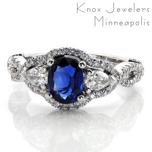 The two adjacent pear shaped diamonds accent the rich, velvety blue of the sapphire. micro pavé diamonds trace the outside edge drawing the eye to the 1.00 carat blue oval center. A slight woven contour gives this custom design a graceful silhouette.