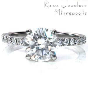 This classic look is exquisitely made in platinum with a hand cut micro pavé band. It currently features a 1.25 carat round center diamond with diamonds in the sides of the setting. The sparkling side stones are simply enthralling and make the design look stunning. This is definitely a head turner!