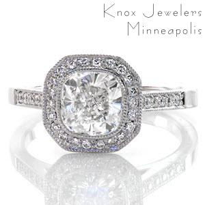 This beautiful halo ring features a 1.20 carat cushion cut center in a full bezel setting. There is micro pavé detailing on the halo, band, and even under the setting of the center diamond! This touch really adds to this splendid design. The look is completed with fine, milgrain on all the edges.