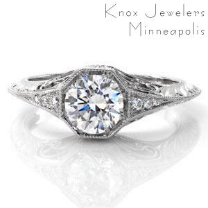 This charming, vintage-inspired design has a 0.75 carat round brilliant cut center diamond in a unique octagonal setting. Side stones taper into a graceful knife-edge band which is edged in milgrain for texture and a refined finish. The sides are adorned with hand engraving, filigree, and diamonds.