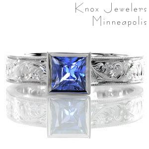 The sumptuous pop of bright blue from the 0.75 carat princess cut sapphire makes this design simply exquisite. The bezel set stone is accented by a wide band with fascinating hand engraved designs which are intricately carved one line at a time. The edges are given a refined finish with milgrain.