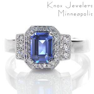 A luxurious deep blue 1.00 carat emerald cut sapphire is the center of attention in this Art Deco inspired piece. The stone is contrasted with bright white micro pavé diamonds set within a halo, as well as in the rectangular bead set shoulder detail. The remaining elements are left high polished.