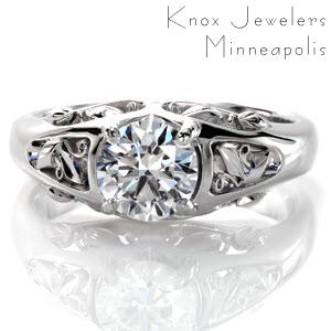 This chic design is a 0.75 carat round brilliant cut diamond solitaire. This eye-catching band is detailed with unique filigree featuring slender scroll curls, leaf patterns, and full ribbon curls. This combination of elements unites beautifully in six different pockets on three sides of the ring.
