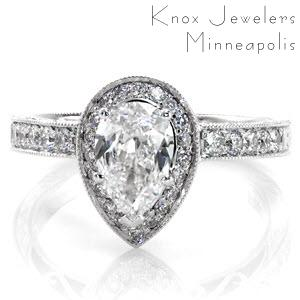 The Pear Valencia is an antique inspired design with a uniquely shaped center stone. The 1.00 carat pear center diamond makes this a statement piece. The micro pavé halo and band are combined with hand engraving and filigree for a timeless feel. The edges of the band are textured with milgrain.