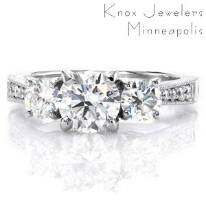 This striking three stone design features a 0.90 carat round brilliant center stone with two .25 carat round side stones. The reverse taper band has micro pavé diamonds trailing off into hand engraving on both the top and side faces. A glamorous five petal diamond detail adds a unique touch.