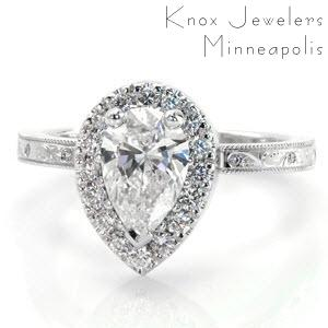 Elegant diamond engagement ring with a pear cut center stone in a micro pave halo. The band is detailed with hand engraving and small flush set round diamonds.