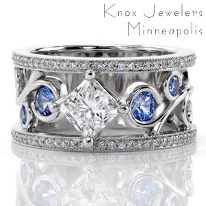This stunning wide band has a radiant pop of color from the blue sapphires set into the curls of the large filigree. The center stone is a kite-set 1.00 carat princess cut diamond that continues the flow of the filigree design. The band is completed with two rows of micro pavé and milgrain edging.